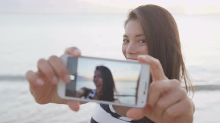 smíšené rasy osoba : Selfie woman taking photos using smartphone having fun outside on beach. Smart phone screen showing as girl takes self portrait photo pictures outdoors at beach sunset. RED EPIC SLOW MOTION. Dostupné videozáznamy