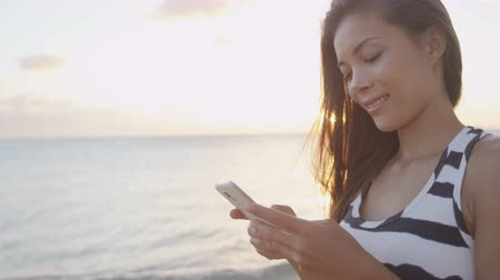 aplikacje : Smartphone woman sms texting using app on smart phone at beach sunset. Mixed race Asian Caucasian girl using smart phone outdoors. Sunshine and flare at ocean beach. Mobile cell phone close up.