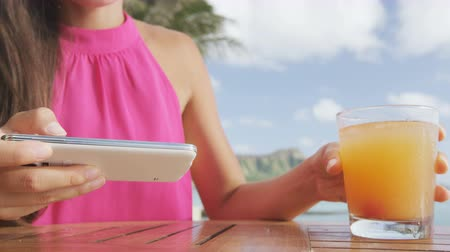 barreaux : Personne utilisant ordinateur tablette appareil intelligent sans fil au bar de la plage potable Mai tai cocktails hawaïens amusant. Gros plan d'une femme tenant boisson alcoolisée dans la plage de Waikiki, Honolulu, Oahu, Hawaii, USA.