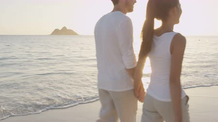 havaiano : Couple holding hands on beach sunset on honeymoon vacation travel. Happy romantic young lovers, man and woman walking on beautiful beach. Lanikai Beach, Oahu, Hawaii, USA. RED EPIC SLOW MOTION.