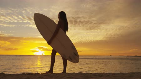 prancha de surfe : Surfer woman in silhouette walking with surfboard at sunset on tropical beach. Surfing girl looking at ocean sunset. Female bikini woman by water standing with surfboard in healthy active lifestyle.