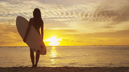 серфер : Surfer girl surfing looking at ocean beach sunset. Silhouette of female bikini woman looking at water with standing with surfboard having fun living healthy active lifestyle. Water sports with model. Стоковые видеозаписи