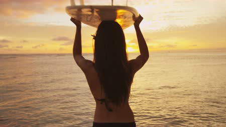 серфер : Young female sYoung female surfer going surfing holding surfboard at sunrise. Beautiful ethnic mixed race Asian Chinese  Caucacsian woman sport model. Sun flare and colorful silhouette. RED EPIC.urfer going surfing surfboard