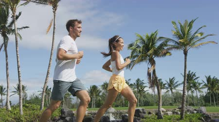 jogging : Running young couple in the park training. Happy active young fit sport adults jogging with tropical background in city or resort. Asian and Caucasian woman and man. Stock Footage