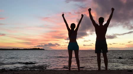 dosažení : Success, achievement and accomplishment concept with fitness people cheering and celebrating of joy with arms raised outstretched up by ocean beach outside. Fitness couple having fun at sunset.