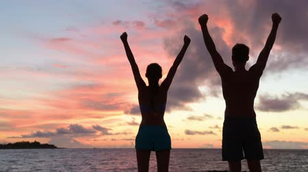 braços levantados : Success, winning and achievement and accomplishment concept with fitness people cheering and celebrating of joy with arms raised outstretched up by ocean beach outdoors. Fitness couple at sunset.