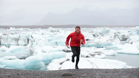 ультра : Running man. Trail runner training running uphill in beautiful nature landscape. Fit male athlete jogging and cross country running  by icebergs in Jokulsarlon glacial lake in Iceland.