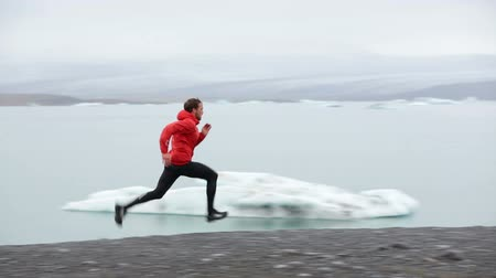 kimerül : Running man sprinting on trail. Runner in fast sprint in beautiful nature landscape. Fit male athlete sprinter cross country running by icebergs in Jokulsarlon glacial lake in Iceland.