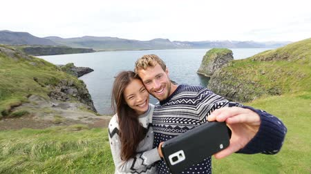 pulóver : Tourists on travel taking selfie self portrait photo with smartphone on Iceland. Happy couple sightseeing taking pictures using smart phone visiting Arnarstapi, Snaefellsnes, Iceland.