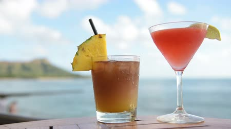 bebida alcoólica : Drinks cocktails on tropical beach. Alcoholic drink close up on Waikiki Beach, Oahu, Hawaii. Typical Hawaiian drinks including Mai Tai. Stock Footage
