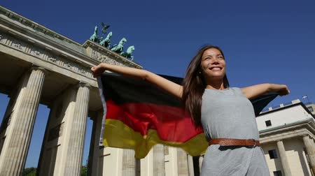 kutluyor : German flag - Woman happy at Berlin  Germany  Brandenburg Gate cheering celebrating waving flag by Brandenburger Tor. Cheerful excited multiracial woman in Germany travel concept. Stok Video