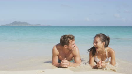 медовый месяц : Beach couple laughing having fun with water splashing lying in sand in water edge. Woman and man on honeymoon relaxing having a good time on pristine white paradise beach. Asian woman, Caucasian man.