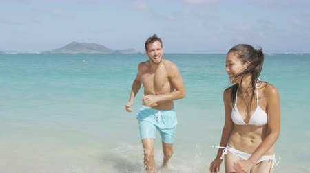 медовый месяц : Happy couple having fun on beach running out of water laughing during summer vacation holiday. Multiracial beautiful couple on honeymoon the sun. RED EPIC SLOW MOTION, 96 FPS.