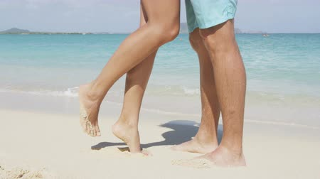 casal heterossexual : Kissing couple in romantic embrace kiss on beach. Young love concept with lovers kissing. Close up of feet and legs as woman is tip toeing for a kiss. Romantic woman and man on vacation summer travel.