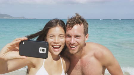 two people : Happy couple in love - Beach smartphone selfie. Young people using smart phone taking self portrait picture on pristine paradise beach. Asian woman, Caucasian man laughing having fun. 96 FPS.