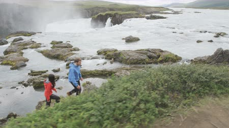 поход : Hiking couple in nature on Iceland on hike by waterfall Godafoss. People enjoying outdoor active healthy lifestyle on travel visiting  landmarks in Icelandic nature. RED EPIC. Стоковые видеозаписи