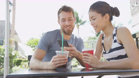 smíšené rasy osoba : Couple on cafe looking at smart phone app pictures drinking coffee in summer. Young urban man using smartphone smiling happy to casual asian woman sitting outdoors. Friends in late 20s. Dostupné videozáznamy