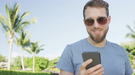 smartfon : Man sms texting using app on smart phone outdoors in summer. Handsome young casual man using smartphone smiling happy wearing sunglasses. Urban male hipster. RED EPIC 90 FPS.