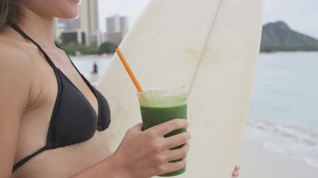ćwiczenia : Green detox smoothie - healthy woman drinking vegetable smoothie after surfing workout on summer day on beach. Fitness and healthy lifestyle concept with beautiful fit surfer model. RED EPIC 96 FPS. Wideo