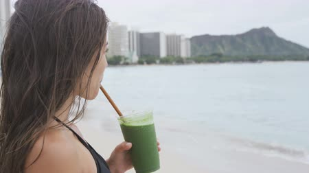 meyve suyu : Vegetable green detox cleanse smoothie - Woman drinking after swimming workout on summer day. Girl drinking green juice or smoothie in fitness and healthy lifestyle concept. Beautiful model on beach. Stok Video