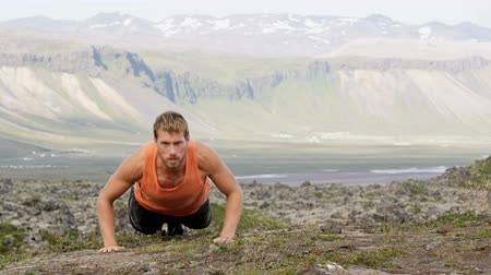 толчок : Fitness push-ups man doing pushups outdoors in nature background. Focused male athlete showing determination and endurance exercising muscles during body core crossfit workout in summer landscape.