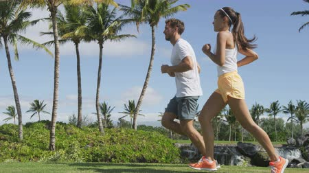 tiro : Running People. Slow motion video of multiethnic young couple jogging in park. Full length of man and woman are in sports clothing. They are representing their healthy lifestyle.