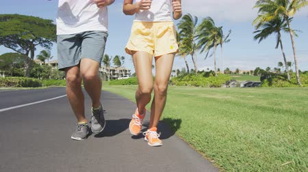 lento : Running People. Low section of multiethnic young couple jogging in park. Slow motion video of man and woman are running on footpath. They are in sports clothing. Couple living their healthy lifestyle. Vídeos