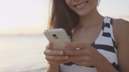 telefones : Cropped video of woman sms texting or using mobile app. Female is using mobile phone at beach during sunset. Sun is shining in background. Girl is smiling while using smartphone.