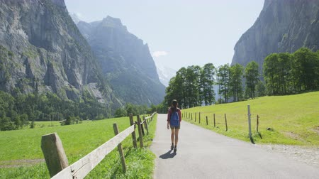 švýcarský : People walking in Switzerland alps. Woman hiker tourist hiking on hike in Swiss alpine nature landscape in Lauterbrunnen valley in Bernese Oberland, Schweiz, Europe.