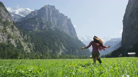 boldogság : Happy woman having fun running in field nature excited of joy happiness. Joyful active lifestyle with free girl enjoying freedom, Lauterbrunnen valley, Swiss Alps, Switzerland. RED EPIC SLOW MOTION