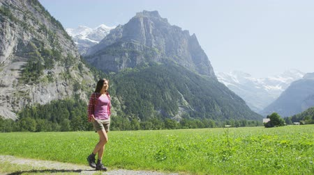 Woman hiking in Switzerland alps landscape. Female hiker tourist on hike in Swiss alpine amazing nature landscape in Lauterbrunnen valley in Bernese Oberland, Schweiz, Europe. RED EPIC SLOW MOTION. Стоковые видеозаписи