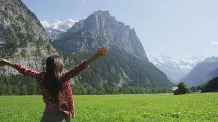 boldogság : Happy free woman with arms outstretched in freedom nature excited of joy happiness. Cheerful active lifestyle with girl serene rasing arms in Lauterbrunnen valley, Swiss Alps, Switzerland. SLOW MOTION Stock mozgókép