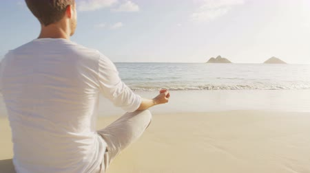 размышлять : Yoga people meditating in lotus pose relaxing outside on beach at sunrise. Couple woman and man in meditation in serene ocean landscape. Lanikai beach, Oahu, Hawaii, USA.