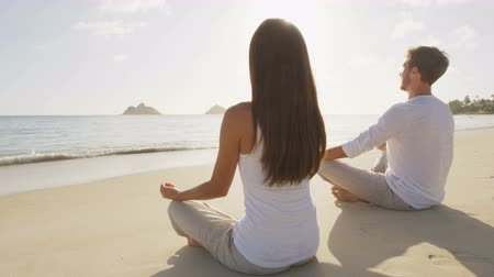 Yoga couple meditating in lotus pose relaxing outside on beach at sunrise. People woman and man in meditation in serene ocean landscape. Lanikai beach, Oahu, Hawaii, USA.