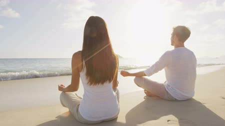 размышлять : Yoga people meditating in lotus pose relaxing outside on beach at sunrise. Couple woman and man in meditation in serene ocean landscape. Стоковые видеозаписи