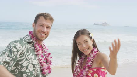 приехать : Hawaii beach couple saying welcome and come here showing hand gesture waving hand gesturing. Portrait of Asian woman and Caucasian man on beach Aloha Hawaiian shirt with flower leis and typical attire