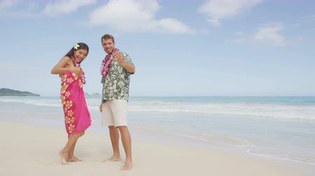 жест : Hawaii beach couple saying welcome and come here showing hand gesture waving hand gesturing. Portrait of Asian woman and Caucasian man on beach Aloha Hawaiian shirt with flower leis and typical attire