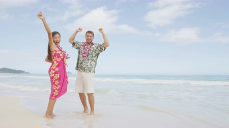 havaiano : Cheering celebrating winning couple on Hawaii beach beach on Hawaiian vacation. Asian woman and Caucasian man wearing flower lei garland and Aloha clothing rasing arms up dancing of joy. Vídeos