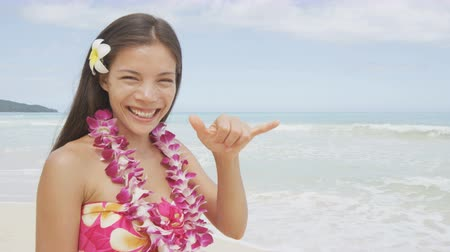 жест : Happy woman girl standing on Hawaiian beach at Hawaii vacation. Asian Caucasian woman wearing flower lei garland and Aloha clothing showing Shaka hand sign on travel.