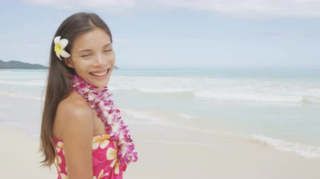 misturado : Woman on beach - smiling happy cheerful. Pretty female model wearing flower lei and sarong enjoying travel vacation holidays in sun. Beautiful mixed race Asian Caucasian girl on Hawaii, United States. Stock Footage