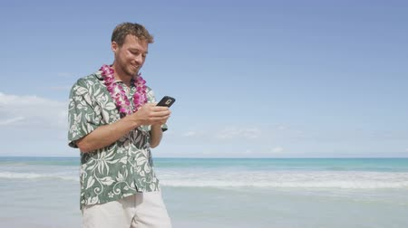 клетка : Man texting using smart phone app on smartphone on Hawaii beach. Handsome young business man working on vacation travel. Urban male professional in Hawaiian clothing wearing Aloha shirt and lei.