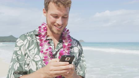 Man texting using smart phone app on smartphone on Hawaii beach. Handsome young business man working on vacation travel. Urban male professional in Hawaiian clothing wearing Aloha shirt and lei.