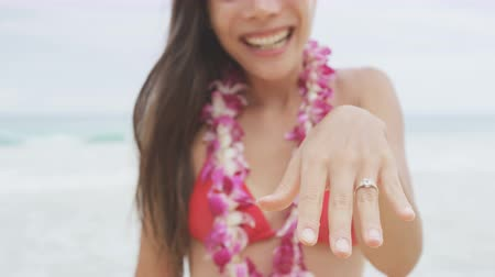 öneri : Engagement ring. Woman showing Engagement ring on beach after marriage proposal. Excited cute girl in wedding concept on Hawaii wearing flower Lei during holiday travel.