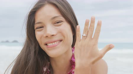 ring : Engagement ring. Woman on beach showing ring after marriage proposal. Excited cute girl in wedding concept on Hawaii wearing flower Lei during holiday travel. Young lovers in love.  Stock Footage