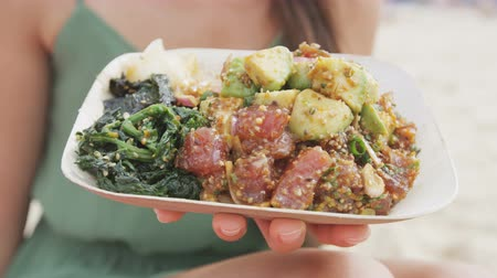 poke : Midsection of woman holding poke salad plate. Closeup of female with traditional Hawaii dish consisting of raw marinated ahi yellowfin tuna fish at beach. Tourist is representing her healthy lifestyle.