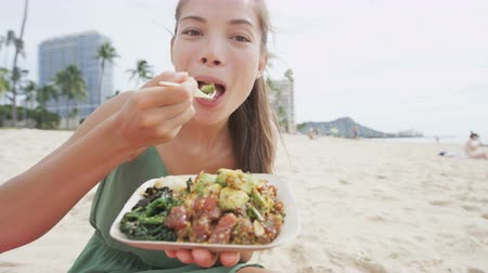 çatal : Smiling young woman eating traditional Hawaiian food. Beautiful female is holding poke salad plate with raw marinated tuna fish. Tourist is representing her healthy lifestyle at beach.