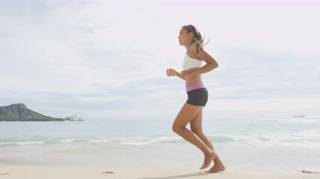 спортивная одежда : Determined young woman jogging on sea shore. Confident female is in sportswear. Jogger is exercising on sunny day. Scenic view of seascape and mountain against sky.