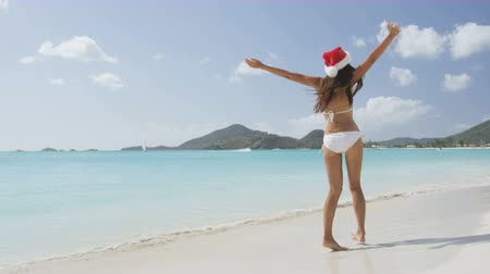 santa : Christmas Santa hat bikini woman on beach vacation holiday getaway. Girl free and happy with arms outstretched of joy on tropical Caribbean beach. Beautiful girl in bikini having fun under the sun.