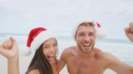 santa : People having fun Christmas beach vacation cheerful - happy couple cheering of joy on and dancing on winter holidays. Young couple wearing santa hat laughing during vacations.  Stock Footage
