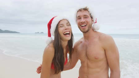 happy holidays : Christmas beach vacation. Happy couple portrait standing on beach laughing having fun on winter holidays. Young couple wearing funny santa hat during vacations. Asian woman.  Stock Footage